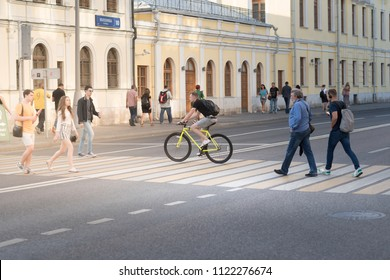 MOSCOW, RUSSIA, 27 JUN 2018. Young man with bicycle with other people crossing road at Volhonka street near the Kremlin
