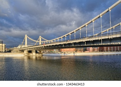 MOSCOW, RUSSIA - Angle view on the sun lighted Krymsky (Crimean) Bridge from Pushkinskaya Embankment of Moskva (Moscow) River (area of Gorky Park) in a winter thaw.