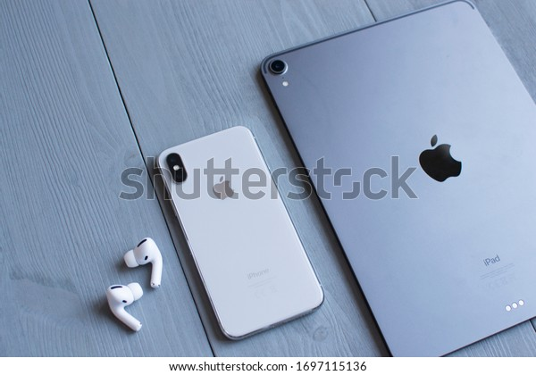Moscow, Russia - April 04, 2020: Charging case and the new iPhone 10 next to New Apple Computers AirPods Pro headphones with Active Noise Cancellation for immersive sound. Ipad pro.