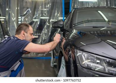 Moscow. Russia. April 06, 2017. A man polishes a black car audi tt