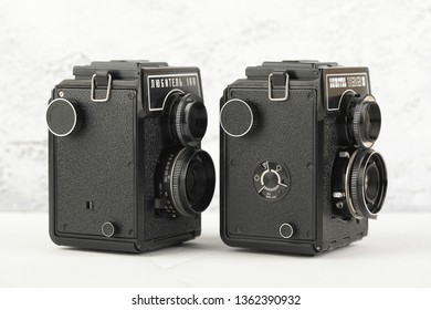 MOSCOW, RUSSIA, APRIL 08, 2019. The old Soviet medium format film TLR cameras Lubitel-166 and Lubitel-166B released at the LOMO factory, cameras for modern lomography on white cement background.
