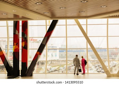 MOSCOW, RUSSIA - APRIL 10, 2016: A young couple looks into a large panoramic window in the shopping center Mega Belaya Dacha in Moscow.