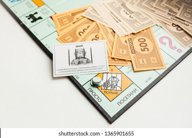MOSCOW, RUSSIA - APRIL 10, 2019: Monopoly board game, paper toy money, prison card, bribery hint