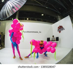 MOSCOW, RUSSIA - APRIL 11, 2019: Unidentified ballet dancers in exotic colored costumes perform a performance at the Gudsen company booth at PhotoForum 2019 exhibition in Moscow, Russia on April 11, 2