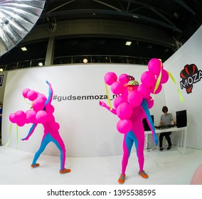 MOSCOW, RUSSIA - APRIL 11, 2019: Unidentified ballet dancers in exotic colored costumes perform a performance at the Gudsen company booth at PhotoForum 2019  in Moscow, Russia on April 11, 2019.