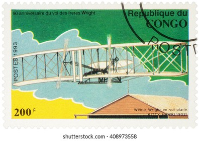 """MOSCOW, RUSSIA - APRIL 15, 2016: A stamp printed in Congo shows Flight Wilbur Wright at Kitty Hawk glider, series """"The 90th Anniversary of the First Powered Flight by the Wright Brothers"""", circa 1993"""