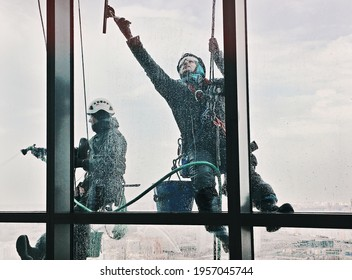 Moscow, Russia - April, 16, 2021: Steeplejacks are cleaning the window of business center.