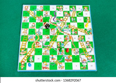 MOSCOW, RUSSIA - APRIL 2, 2019: gameboard of Snakes and Ladders board game on green baize table. Snakes and Ladders is an ancient Indian board game, now it is worldwide classic tabletop game