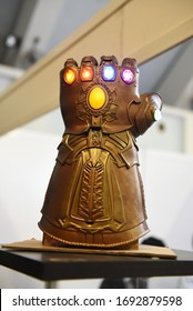 Moscow, Russia - April 2020 : Сlose-Up Of Thanos's Infinity Gauntlet. Huge Gold Glove With Infinity Gems. Thanos - Character Of Fortnight Game, Comic And Marvel Movie, Production By Marvel Studio.