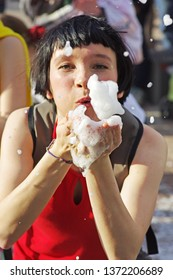 Moscow, Russia - April 22, 2012: Woman blows soap foam from her hands into the camera on a flashmob on Arbat in Moscow