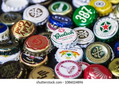 Moscow, Russia - April 22, 2018: Background of beer bottle caps, a mix of various global brands: Grolsch, Bud, Bavaria, Miller, Heineken, Baltika; corona extra etc.