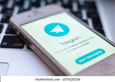 MOSCOW, RUSSIA - APRIL 24, 2018: Mobile phone on laptop keyboard with telegram attachment. From April 16 on the territory of the Russian Federation, the messenger of telegrams