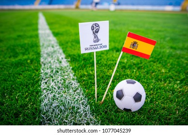 MOSCOW, RUSSIA - APRIL, 24, 2018: Spain national flag and Official logo of Football FIFA World Cup 2018 in Russia. Green grass, edit space in background.
