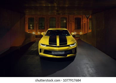 Moscow, Russia - April 24, 2018 Chevrolet Camaro yellow with black stripes at the parking entrance at night