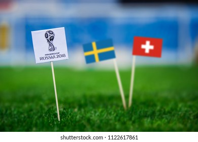 MOSCOW, RUSSIA - APRIL, 24, 2018: Sweden - Switzerland, Round of 16, eight final, 3. July, Football FIFA World Cup, Russia 2018, National Flags on green grass, white football ball on ground. Play-off