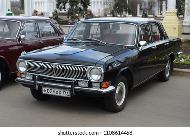 MOSCOW, RUSSIA - APRIL 25, 2015: USSR cars open air exhibition in VDNKh. Volga GAZ-24 soviet car with communist style background.