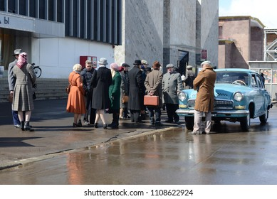 MOSCOW, RUSSIA - APRIL 25, 2015: USSR 1960s style street in VDNKh with soviet buildings and people. White Blue GAZ-21 taxi car in front of communist style building.