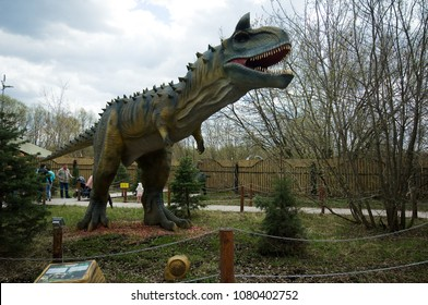 MOSCOW, RUSSIA - APRIL 29, 2017: Unidentified people resting near Carnotaurus in Dinosaur Park, Moscow, Russia