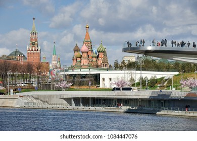 MOSCOW, RUSSIA - April 29, 2018 View from Raushskaya embankment on pier and hovering bridge of Zaryadye park over Moskva (Moscow) River in the background of St. Basil's Cathedral and Spasskaya tower