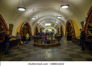 MOSCOW, RUSSIA- APRIL, 29, 2018: Unidentified people going downstairs and walking close to the bronze sculpture in Ploshchad Revolyutsii subway station