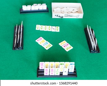 MOSCOW, RUSSIA - APRIL 3, 2019: gameplay of Rummy tile-based card game on green baize table. Rummy is tile and card game based on matching cards of the same rank or sequence and same suit