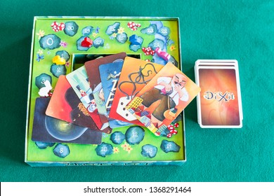 MOSCOW, RUSSIA - APRIL 3, 2019: card deck and pictures on box of Dixit board game on green baize table. Dixit is a card game created by Jean-Louis Roubira and first published by Libellud in 2008