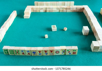 MOSCOW, RUSSIA - APRIL 3, 2019: player's set at the beginning of mahjong game , tile-based chinese strategy board game on green baize table