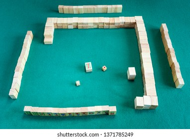 MOSCOW, RUSSIA - APRIL 3, 2019: beginning of play of mahjong (disassembling the wall), tile-based chinese strategy board game on green baize table