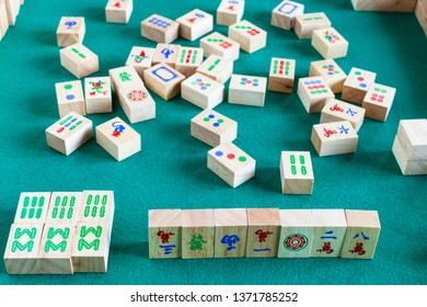 MOSCOW, RUSSIA - APRIL 3, 2019: gameplay of mahjong game, tile-based chinese strategy board game on green baize table