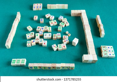 MOSCOW, RUSSIA - APRIL 3, 2019: above view of gameboard of mahjong game, tile-based chinese strategy board game on green baize table
