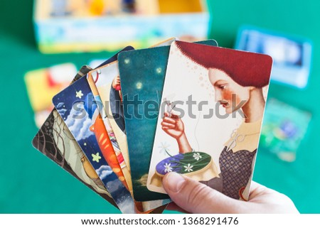 MOSCOW, RUSSIA - APRIL 3, 2019: player shows picture cards in Imaginarium game. Imaginarium is card game for stories and associations, russian variant of Dixit game