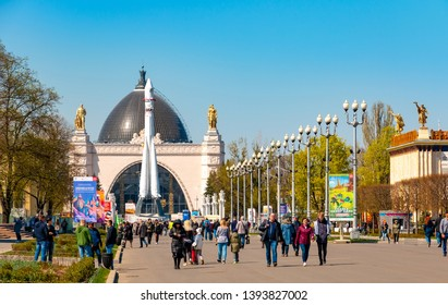 Moscow, Russia - April 30, 2019: Tourists in the city park VDNH and rocket Vostok 1 with Pavilion 34 Cosmos or Mechanization in the background