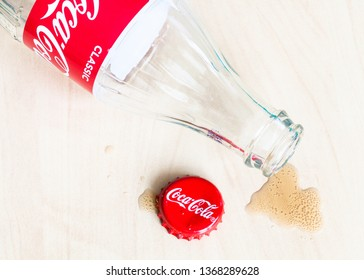 MOSCOW, RUSSIA - APRIL 4, 2019: red crown cap, empty bottle from Coca-Cola beverage and spilled puddle on wooden table. Coca-Cola (Coke) is carbonated soft drink manufactured by The Coca-Cola Company