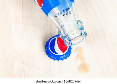 MOSCOW, RUSSIA - APRIL 4, 2019: used crown cap, neck of empty bottle from Pepsi beverage and spilled puddle on wooden board . Pepsi is carbonated soft drink manufactured by PepsiCo
