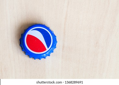 MOSCOW, RUSSIA - APRIL 4, 2019: used crown cork bottle cap from Pepsi beverage on wooden board with copyspace. Pepsi is carbonated soft drink manufactured by PepsiCo