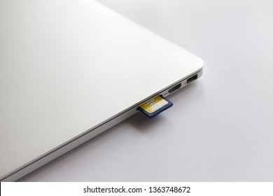 Moscow / Russia - April 5, 2019: MacBook Pro on a white table. Transcend SD 2GB memory card inserted into card reader
