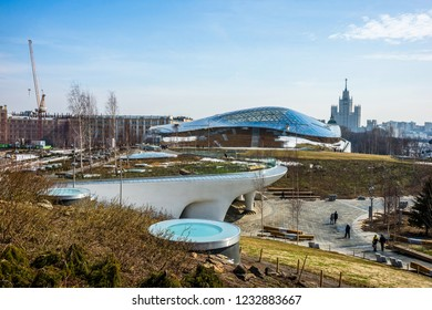 MOSCOW, RUSSIA - April 6, 2018. Zaryadye Park landscape in early spring sunny day: Amphitheater and Kotelnicheskaya Embankment Building on the horizon.