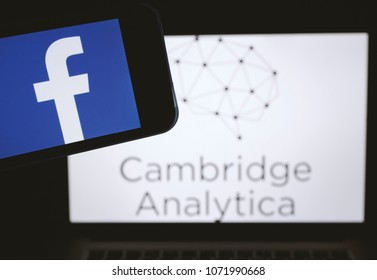 Moscow, Russia - April,19: The logo of the strategic communication company Cambridge Analytica is seen on the screen of an iPhone in front of a computer screen showing Facebook logo