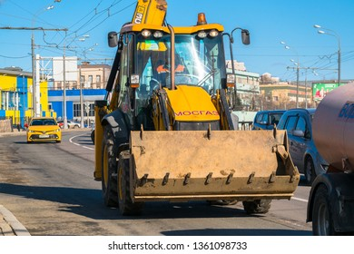 MOSCOW, RUSSIA, APRIL,2.2019: Widespread model of the universal backhoe loader of JCB Company (Great Britain).Traffic on city streets