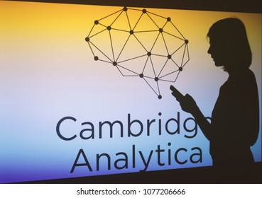 Moscow, Russia - April,26: A woman is seen as a silhouette as she checks a mobile device in front of a screen showing  the logo of the strategic communication company Cambridge Analytica