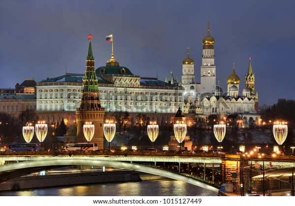 MOSCOW, RUSSIA - Architectural ensemble of Moscow Kremlin and Bolshoy Kamenny Bridge decorated with wineglass-shaped street lamps during winter holidays in twilight. View from Pariarchy bridge.