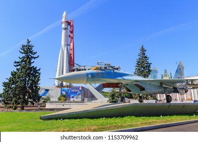 Moscow, Russia - August 01, 2018: Russian fighter SU-27 on a background of Vostok booster rocket on Exhibition of Achievements of National Economy (VDNH) against blue sky on a sunny summer morning
