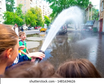 MOSCOW, RUSSIA - AUGUST 07, 2019: Fire station. Happy kids acting like a fireman holding firehose nozzle and splashing water.