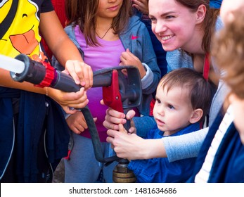 MOSCOW, RUSSIA - AUGUST 07, 2019: Happy kids acting like a fireman holding firehose nozzle and splashing water.Child in a school group of children and adults with hose in hands playing firefighter.