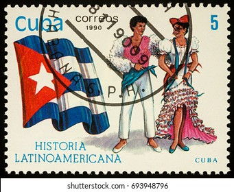 """Moscow, Russia - August 10, 2017: A stamp printed in Cuba, shows national flag and a couple in traditional costumes of Cuba, series """"Latin-American History"""", circa 1990"""