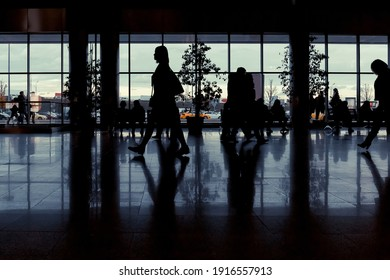 MOSCOW, RUSSIA, August 10, 2019: Dark silhouettes of people against the background of large light windows. Horizontal view.
