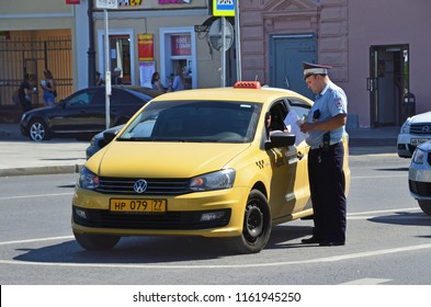 Moscow, Russia, August, 12, 2018. Traffic police officer checks the documents of a taxi driver on the Big Sukharevskaya square in Moscow