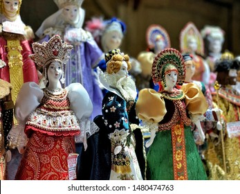 Moscow, Russia - August 15, 2019: Collectables handmade porcelain dolls standing in traditional Russian clothes. Made of porcelaine, hand-painted and sold as a souvenir.