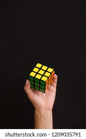 Moscow, Russia, August 16 2017: Girl holding colorful cube and playing with it on black background. Rubik's cube in young woman's hand.