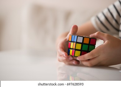 Moscow, Russia, August 16 2017: Rubik's cube in child's hands, closeup. Boy holding Rubik's cube and playing with it.